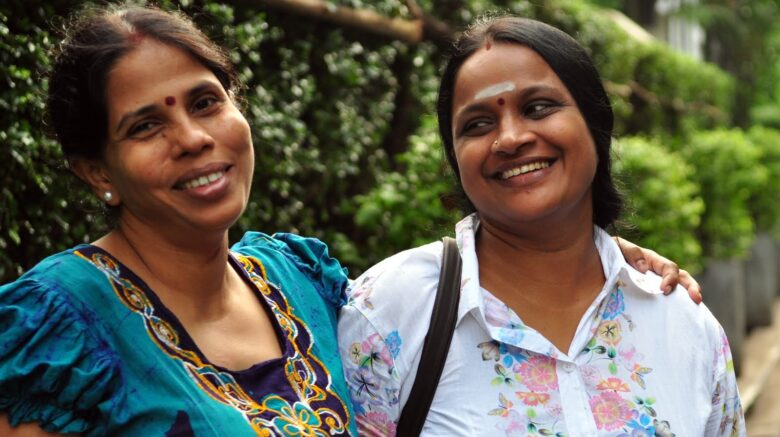 Image shows two women smiling together