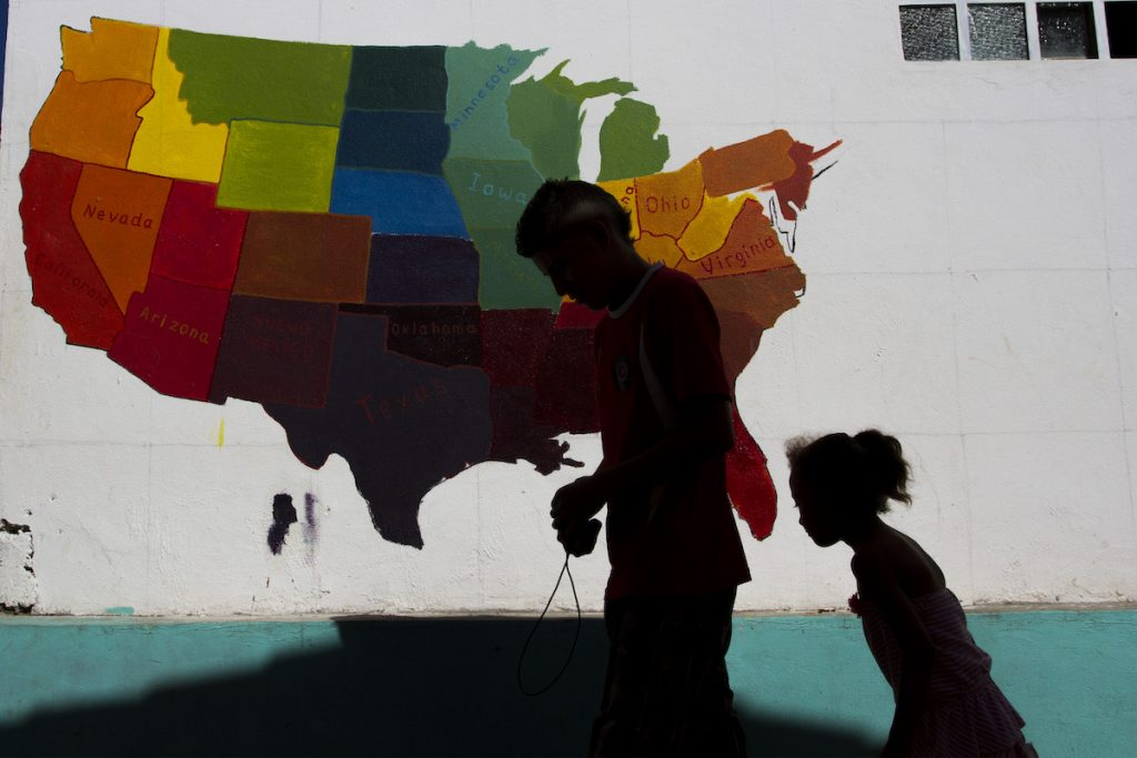 Image shows a father and daughter walking past a painted map of the United States