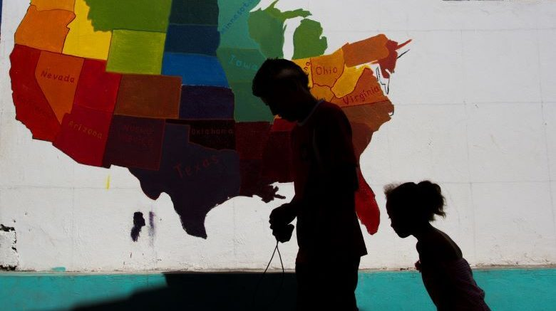 Image shows father and daughter in front of a map of the United States.