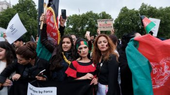 Image shows three Afghan women holding Afghan flags at a protest