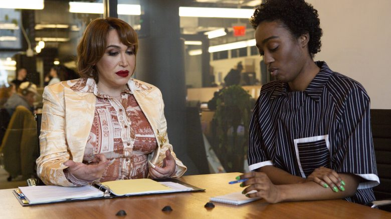 A Latina trans woman and a Black non-binary person sitting together at a meeting table